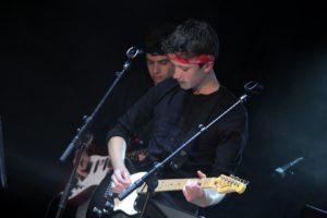 deux guitaristes derrière un micro