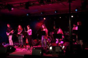 Groupe de 6 musiciens sur scène éclairage rouge