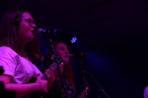 deux jeunes musiciennes chantent, une avec un ukulele l'autre avec un saxophone