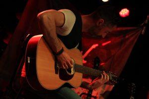 Guitariste jouant de la guitare sèche sur scène avec lumière rouge