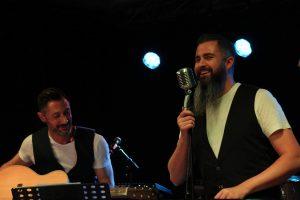 Un chanteur et un guitare rient sur scène